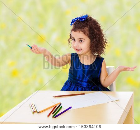Adorable little girl in a blue dress drawing pencils . Girl sitting at the table.Bright, floral yellow-green blurred background.