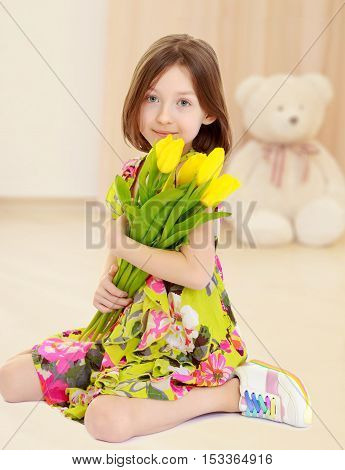 Adorable little Caucasian girl in summer dress holding a bouquet of yellow tulips.In the children's room in which sits a Teddy bear.