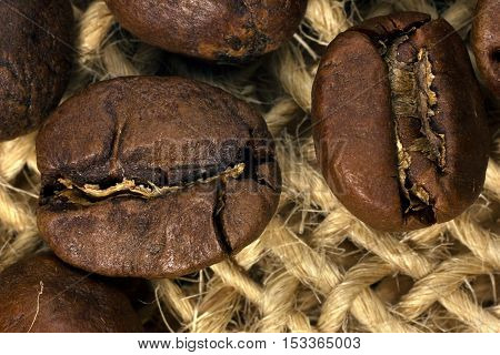 Coffee beans closeup on natural texture to design kitchens, cafes, shops