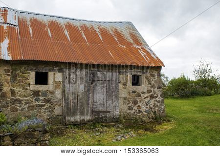 Rustic old barn made from stone against a cloudy sky in Brittany France