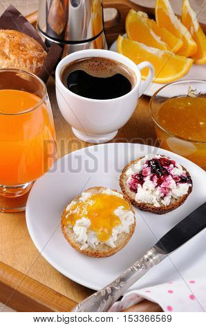 Breakfast of bun with ricotta orange and cherry jam