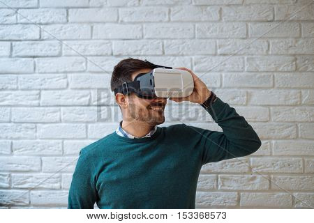 Handsome man trying VR glasses at home.