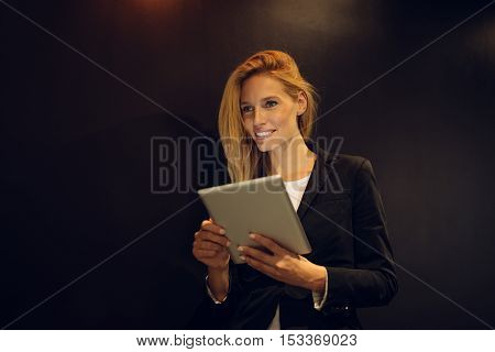 Attractive businesswoman working overtime in an office.