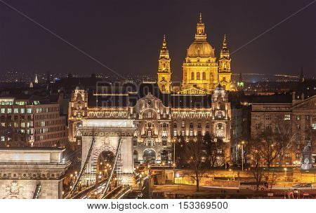 Night View of the Szechenyi Chain Bridge over Danube River and church St. Stephen's Basilica in Budapest Hungary.
