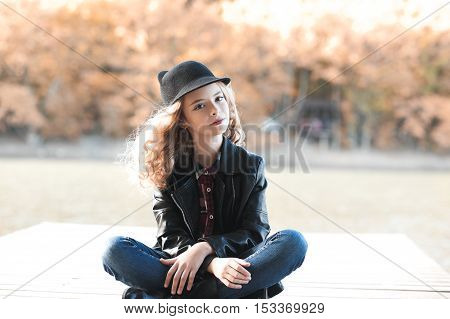 Stylish teen girl 12-4 year old wearing trendy casual clothes sitting outdoors. Looking at camera.