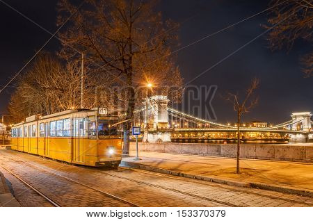 BUDAPEST HUNGARY - FEBRUARY 22 2016: Night view of the tram on the background of the Chain Bridge in Budapest Hungary.
