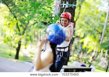Asian girl and a guy are briefed on the passage of the rope way to the amusement park.