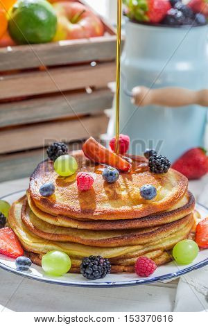 Pancakes with fruits poured maple syrup on old wooden table