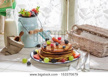 American pancakes with fruits and maple syrup