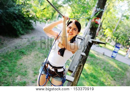 Asian girl in special equipment passes obstacles in the ropes course on the background of trees