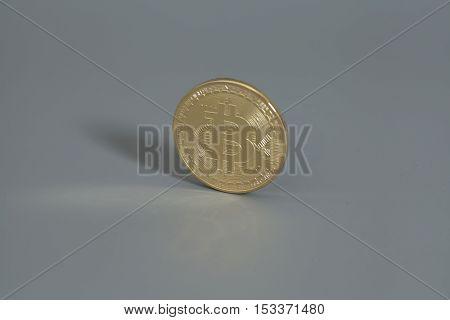 Golden Bitcoin coin on a gray background