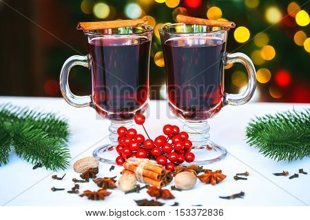 Beautiful Two Glasses Of Mulled Wine Standing On The Background Of A Blurred Decorated Christmas Tre