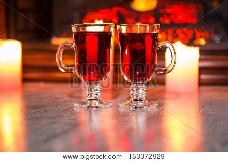 Beautiful Two Glasses Of Mulled Wine On Bokeh Background With Candles And A Fireplace. The Idea For
