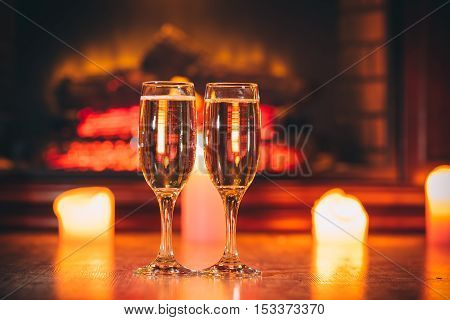 Beautiful Two Glasses Of Champagne On Blurred Background With Candles And A Fireplace. The Idea For