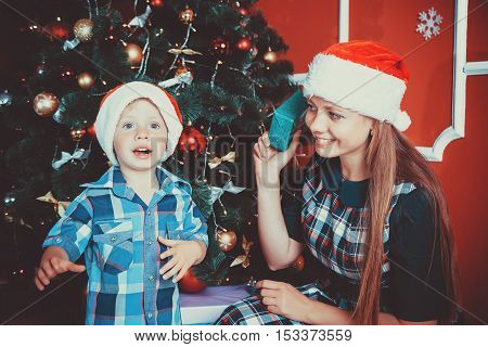 Beautiful Portrait Of Happy Mother And Son On The Background Of The Christmas Tree In New Year Room
