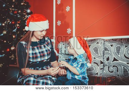 Beautiful Portrait Playing On The Sofa Mother And Son In Santa Hats At The Christmas Tree In New Yea