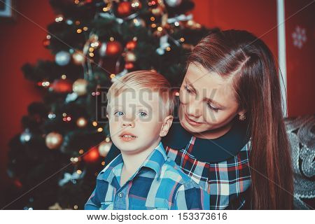 Beautiful Portrait Of Happy Mother And Son On The Background Of The Christmas Tree In New Year Room.