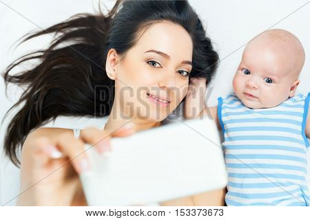 Funny baby and mother make selfie on mobile phone and lying near her mother on a white bed. Newborn looking at the camera and smiling. Mothercare is most important in baby life