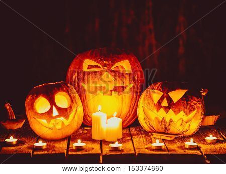 Halloween Pumpkins Head Jack Lantern With Candles Around On The Old Boards In A Spooky Night Landsca
