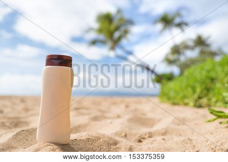 Blank sunscreen sun lotion bottle lying in golden sand on hawaii beach vacation tropical background. Sunny summer day with sunblock cream plastic container - uv protection skincare concept.
