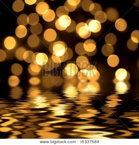 Gold spots bokeh background reflected in the water