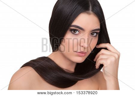 Young beautiful girl with long hair around the neck and bare shoulders looks into the camera.