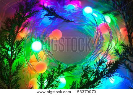 out of focus colored lights and garlands of Christmas tree branches. New Year Christmas background