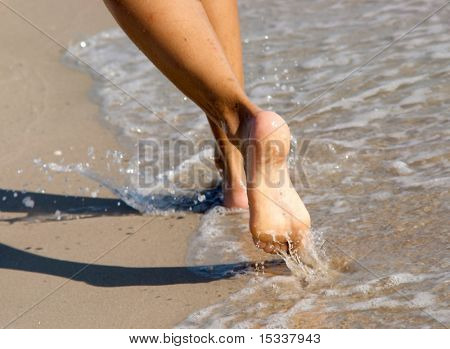 Women's barefoot legs on the beach