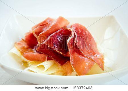 Becon and melon. Ham. Traditional Spanish dish - jamon Serrano and prosciutto crudo sliced with melon.