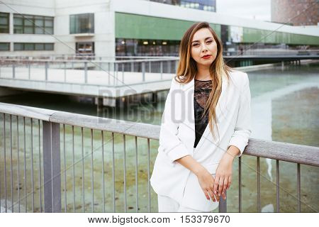 Portrait of fashionable well dressed woman with long hair is posing outdoors near urban area, looking into the camera. Elegant lady in white suit standing near modern buildings