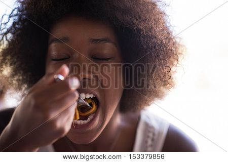 young beautiful African American woman enjoys while eating delicious pasta