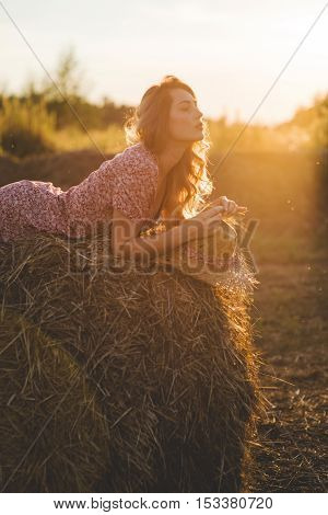 Beautiful young woman on a haystack at sunset