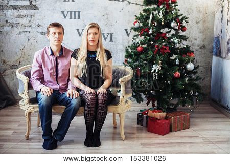 boy and girl sitting on the couch modestly. The concept of Christmas and New Year