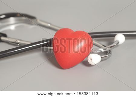 Red heart with a medical stethoscope on gray background