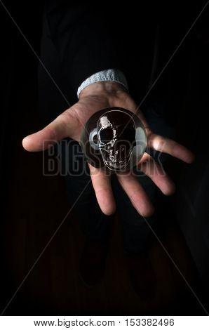 Holding magic crystal ball with skull predicting death
