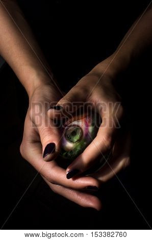 Female hands hold crystal ball with third eye for fortune telling background