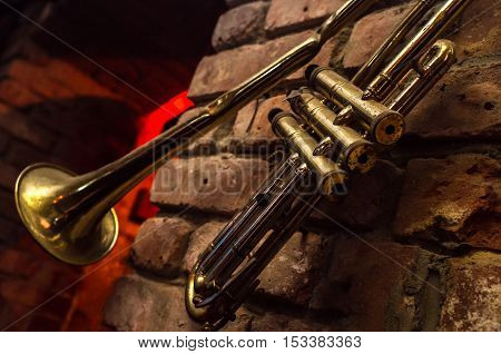 Old bent jazz trumpet hangs on grunge brick wall outside club
