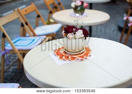 Vase with white and red flowers standing on white wooden table in cafe outdoors street.