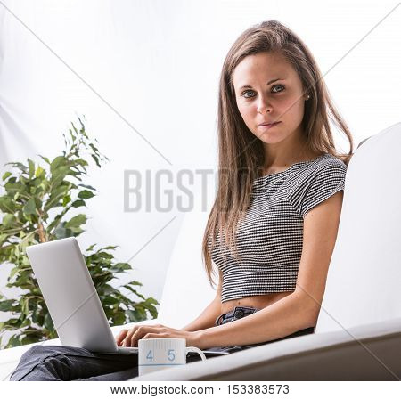 portrait of a young woman working on a notebook at home in her living room on a white sofa