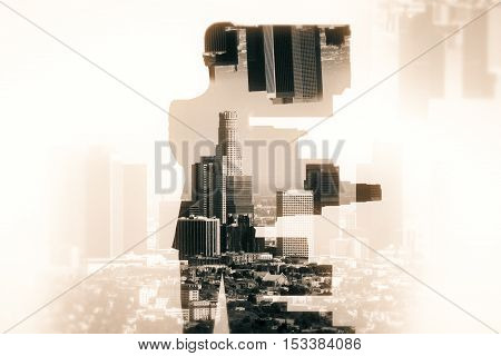 Back view of businessman silhouette on abstract city background. Double exposure