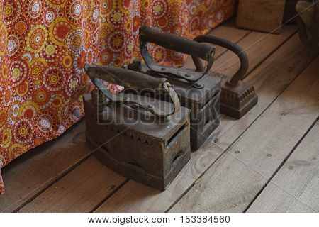 Ancient Irons On A Timber Floor