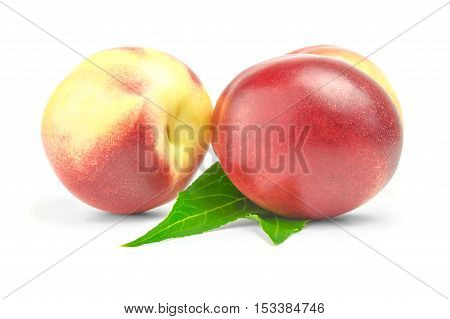 two ripe nectarines with green leaves over white background.