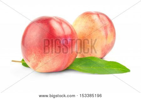 two nectarines with green leaves over white background.