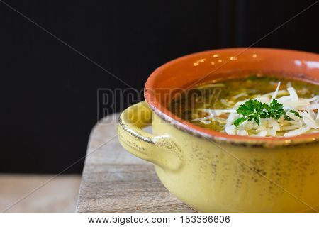 Bowl of vegetable soup in a yellow and orange crock on a wooden board with copy space on left