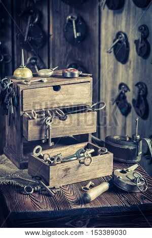 Aged locksmiths workshop with ancient tools on old wooden table