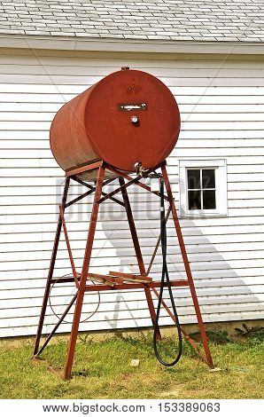 A brightly painted old fuel barrel on an a stand with a hose to fill tractors and farm engines