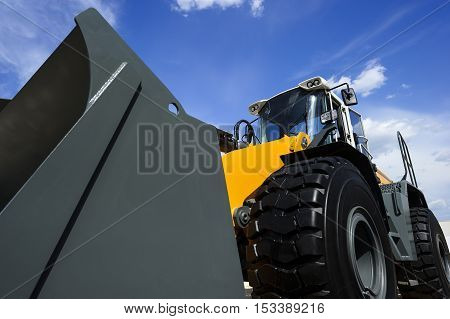 Bulldozer, huge yellow powerful construction machine with big grey scoop and black wheels, heavy industry, bottom view, blue sky and white clouds on background