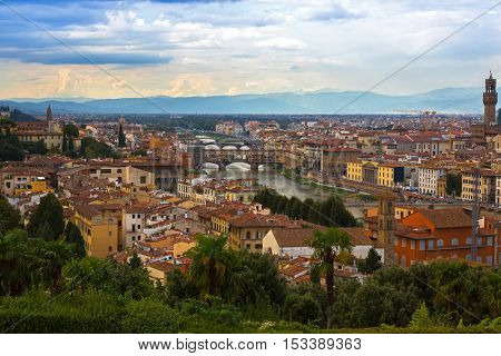 FLORENCE, ITALY - SEPTEMBER 2016 : Cityscape View of Arno river, Ponte Vecchio bridge, clock tower of Old Palace in evening in Florence, Italy on September 21, 2016. View from Michelangelo square
