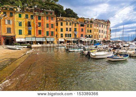 PORTOFINO, ITALY - SEPTEMBER 2016 : Restaurants, shops, colorful historical buildings and many boats at Portofino port, Italian fishing village, Genoa province, Italy on September 23, 2016.