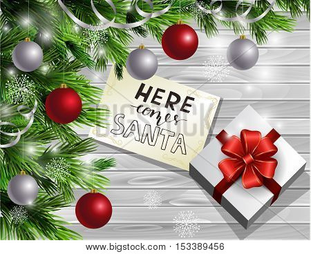 Christmas New Year design light wooden background with christmas tree and silver and red balls and greeting card with handwritten words Here comes Santa with gift boxes.